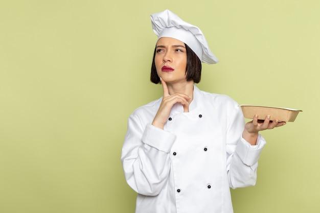 Вид спереди молодая женщина-повар в белом костюме повара и кепке, держащая пакет с мыслящим выражением на зеленой стене, леди, работа, еда, кухня, цвет