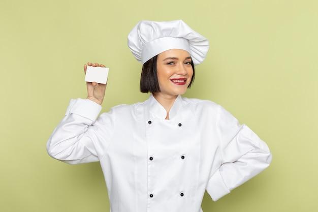 白いクックスーツと緑の壁の女性に白いカードを保持しているキャップで正面の若い女性クックは、食品料理の色を仕事します。