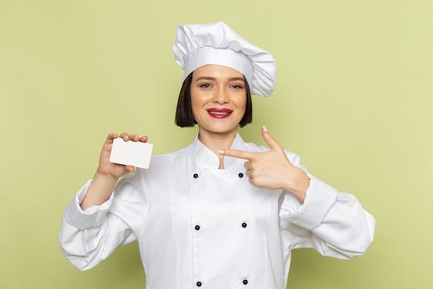 緑の壁に笑顔で白いクックスーツと白いカードを保持しているキャップで正面の若い女性クック女性の仕事食品料理色