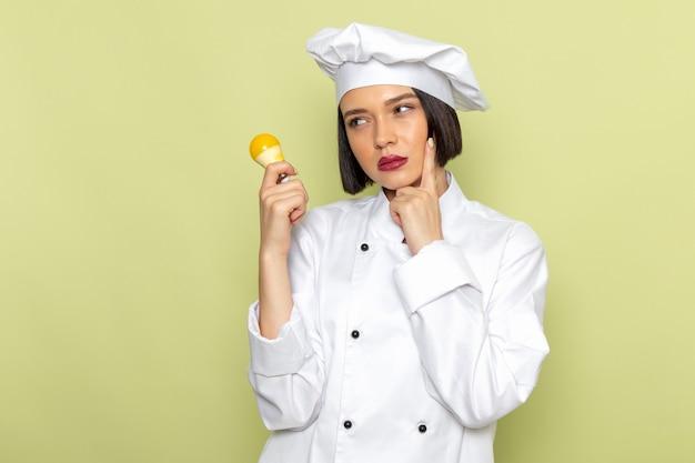 Вид спереди молодая женщина-повар в белом костюме повара и кепке держит желтую лампочку с мыслящим выражением на зеленой стене.