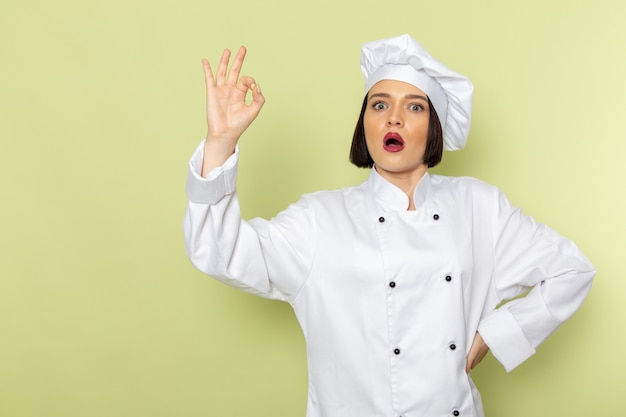 흰색 요리사 양복과 녹색 벽에 포즈 모자에 전면보기 젊은 여성 요리사 레이디 작업 음식 요리 색상