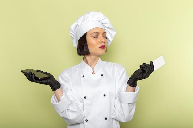 Вид спереди молодая женщина-повар в белом костюме повара и кепке в перчатках и стерильной маске держит телефон на зеленой стене.