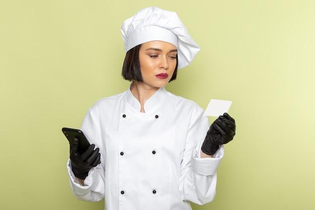 Вид спереди молодая женщина-повар в белом костюме повара и кепке в перчатках с телефоном на зеленой стене.