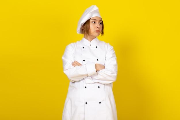 黄色に不機嫌な白いコックスーツと白い帽子の若い女性クックの正面図