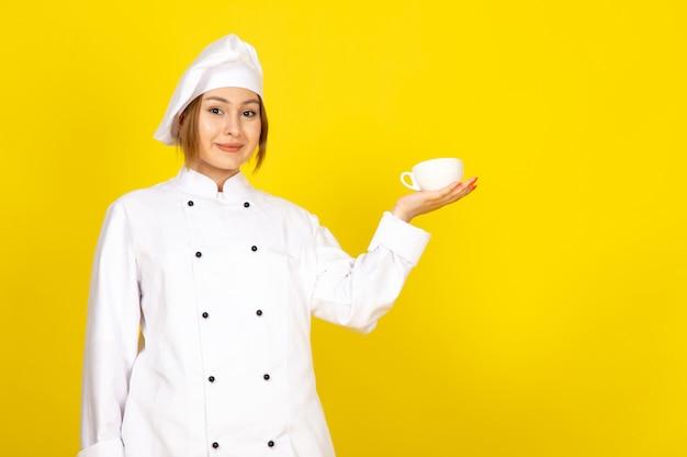Вид спереди молодая женщина-повар в белом поварском костюме и белой кепке пьет, держа чашку кофе, улыбаясь на желтом