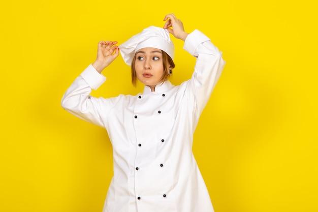 Вид спереди молодая женщина-повар в белом кухонном костюме и белой кепке фиксирует свой костюм на желтом