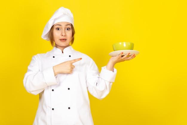 白いコックスーツと黄色の緑と赤のプレートを保持している白い帽子の正面の若い女性クック