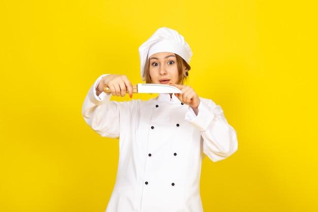 Вид спереди молодая женщина повар в белом поварском костюме и белой кепке держит нож на желтом