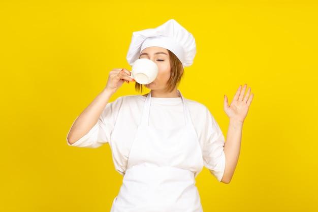 Вид спереди молодая женщина-повар в белом кухонном костюме и белой кепке держит белую чашку и пьет кофе, возбужденный на желтом