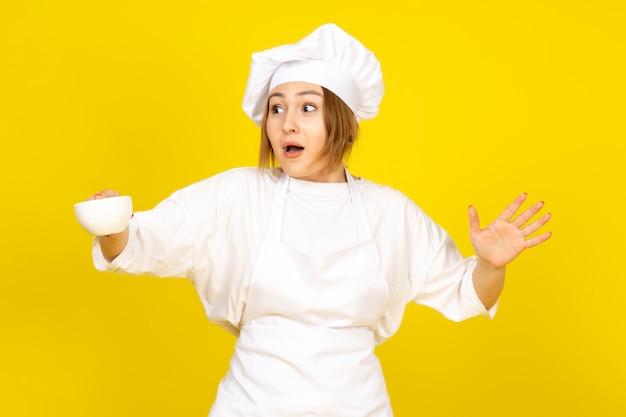 흰색 쿡 양복과 흰색 컵을 들고 흰색 모자에 전면보기 젊은 여성 요리사는 노란색에 재미 흥분