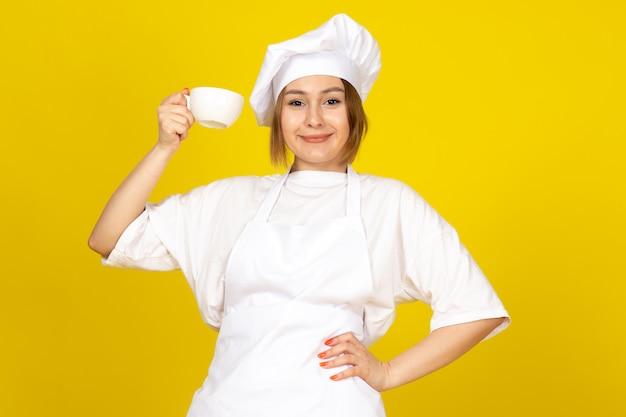 白いコックスーツと黄色に笑みを浮かべて白いカップを保持している白い帽子の正面の若い女性クック
