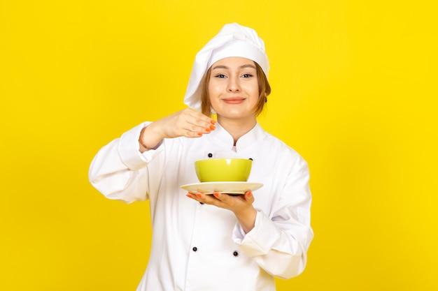 白いコックスーツと黄色と赤のプレートを保持している白い帽子の正面の若い女性クックは黄色に笑みを浮かべて喜んで