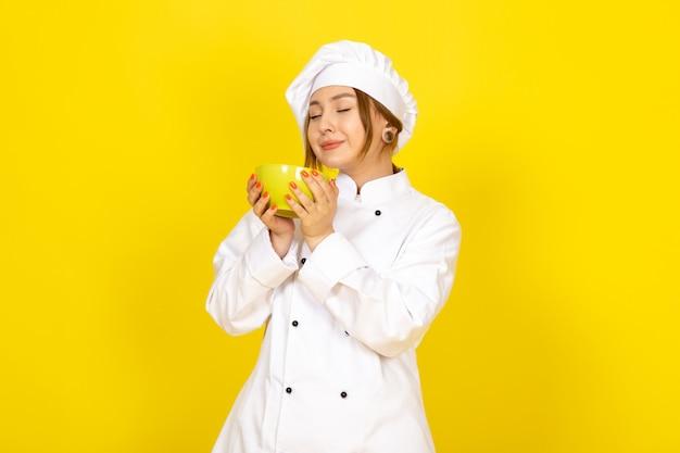 白いコックスーツと黄色のプレートに黄色のプレートを保持している白い帽子の若い女性クックの正面図