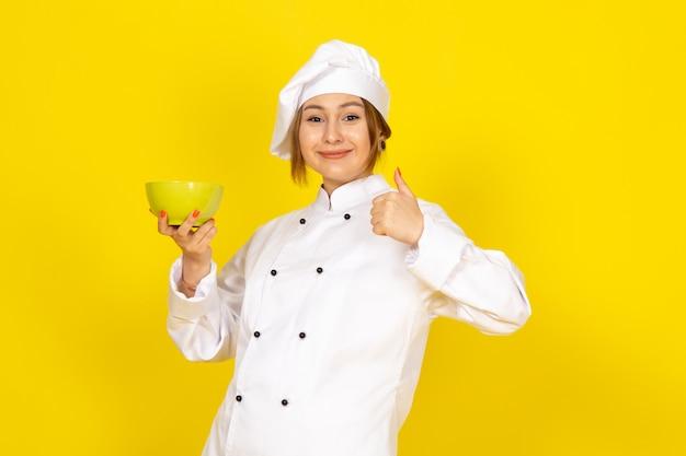 白いコックスーツと黄色いプレートを保持している白い帽子で正面を向いた若い女性料理人が黄色に笑って喜んで