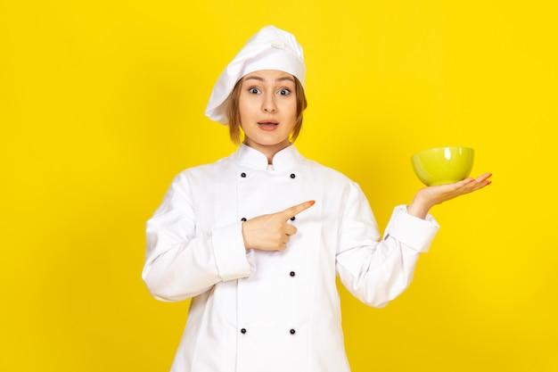 白いコックスーツと黄色の黄色のプレートを保持している白い帽子の正面の若い女性クック