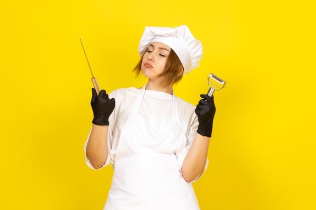 Вид спереди молодая женщина-повар в белом кухонном костюме и белой кепке в черных перчатках с ножом и очистителем овощей на желтом