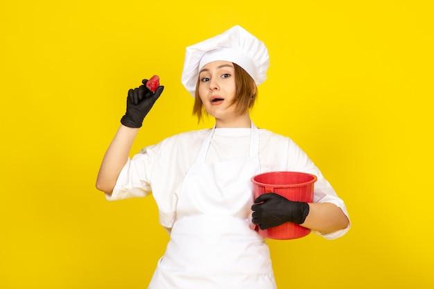 Вид спереди молодая женщина-повар в белом поварском костюме и белой кепке в черных перчатках с красной корзиной на желтом