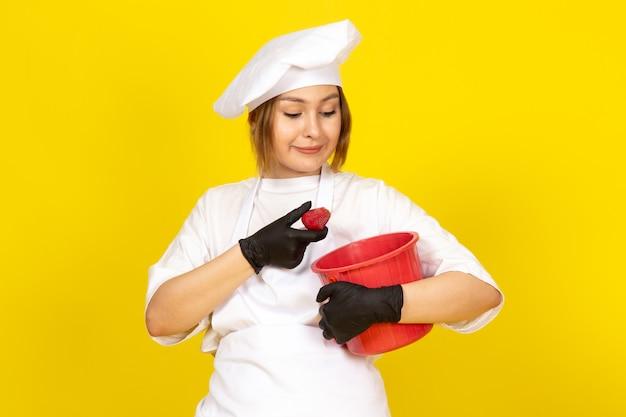 Вид спереди молодая женщина повар в белом поварском костюме и белой кепке в черных перчатках с красной корзиной, улыбаясь на желтом