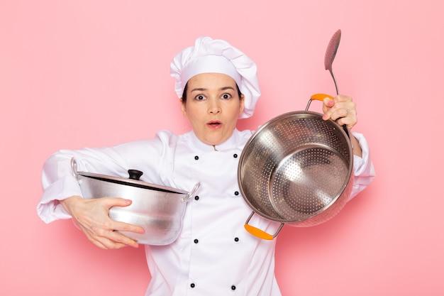 白いクックスーツホワイトキャップポーズ大きな銀のスプーンと銀鍋を保持しているポーズで若い女性クック正面