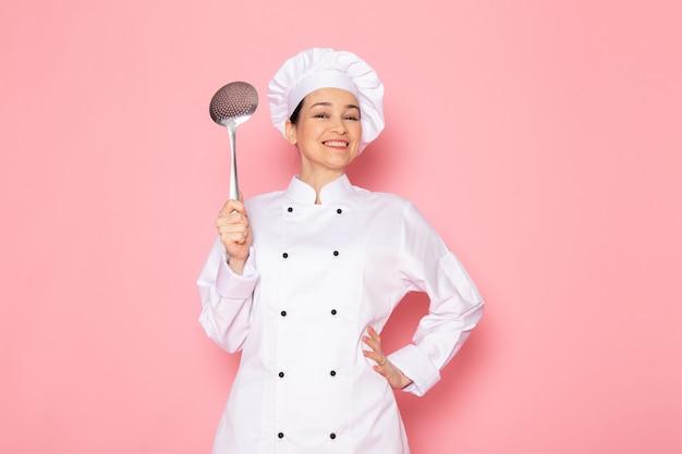 Вид спереди молодая женщина повар в белом костюме повара белая шапка позирует держит большую серебряную ложку, улыбаясь счастливое выражение
