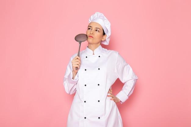 큰 은색 스푼 생각 식을 들고 포즈 흰색 쿡 정장 흰색 모자에 전면보기 젊은 여성 요리사