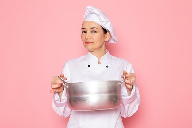 Вид спереди молодая женщина-повар в белом кухонном костюме белая шапочка позирует держа серебряную кастрюлю Бесплатные Фотографии