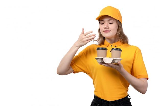 白の香りの臭いがするコーヒーカップを保持しているフードデリバリーサービスの正面の若い女性宅配便女性労働者