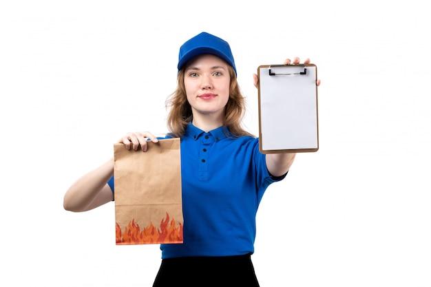 Вид спереди молодой женщины курьер работница службы доставки еды, холдинг пакет продуктов питания и блокнот, улыбаясь на белом