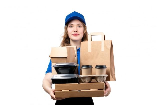 Фронтальный вид молодой женщины курьер работница службы доставки еды, держа пакеты с едой и коробки на белом