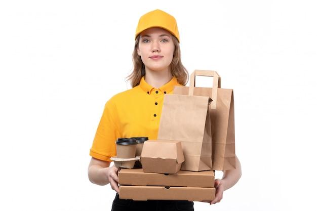 Вид спереди молодой женщины курьер работница службы доставки еды, холдинг коробки для пиццы и пакеты с едой на белом