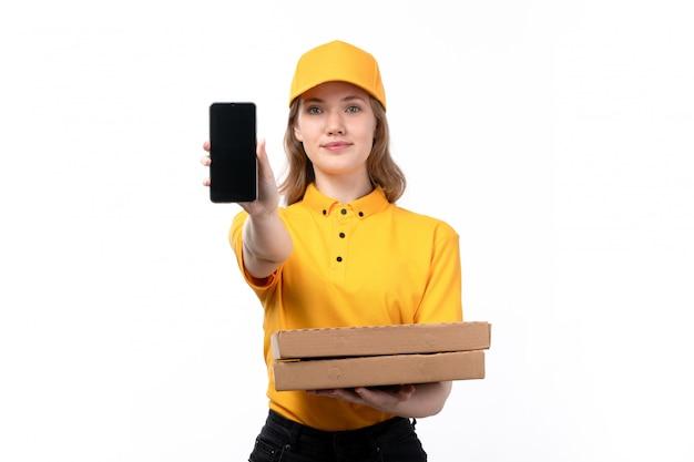 Вид спереди молодая женщина-курьер работница службы доставки еды держит коробки для пиццы и смартфон на белом