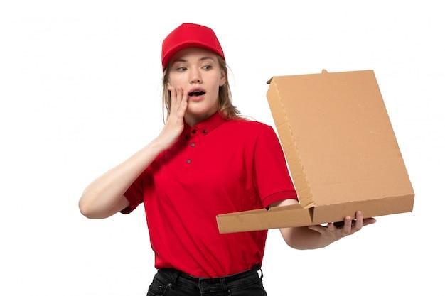 Вид спереди молодая женщина-курьер работница службы доставки еды открытие коробки пиццы с удивленным выражением на белом