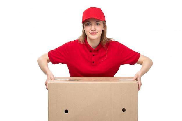 Вид спереди молодая женщина курьер работница службы доставки еды, улыбаясь, держа огромную коробку на белом