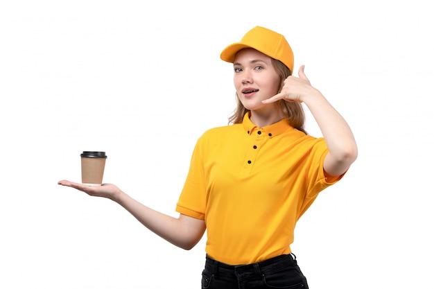 フードデリバリーサービスの正面の若い女性の宅配便の女性労働者がコーヒーを保持しているカップを笑顔で白の架空の電話を使用して