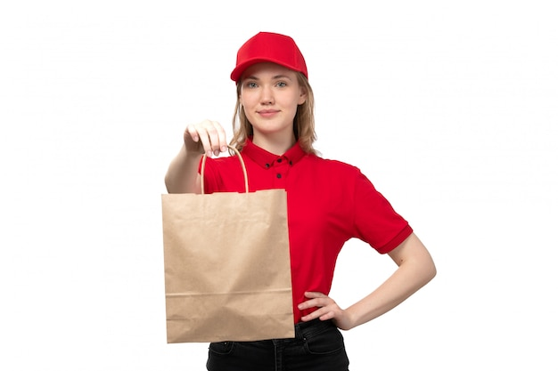 白のフードデリバリーパッケージを保持笑みを浮かべてフードデリバリーサービスの正面若い女性宅配便女性労働者