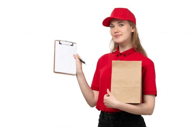 Вид спереди молодой женщины курьер работница службы доставки еды, улыбаясь, держа блокнот и пакет продуктов питания на белом