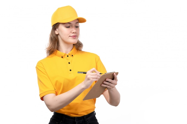Вид спереди молодой женщины курьер работница службы доставки еды, улыбаясь, держа блокнот, записывая заказы на белом