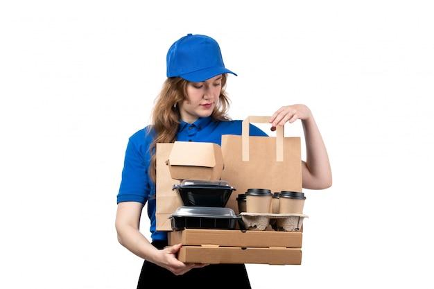 青いシャツの青い帽子とフードパッケージと白のコーヒーカップを保持している黒いズボンの正面の若い女性の宅配便