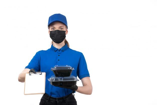 Вид спереди молодой женщины-курьера в синей форме, черных перчатках и черной маске, держащей миски для доставки еды и блокнот