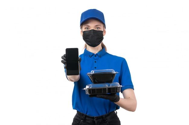 Молодая женщина-курьер в синей униформе, черные перчатки и черная маска, держащая миски для доставки еды и телефон, вид спереди