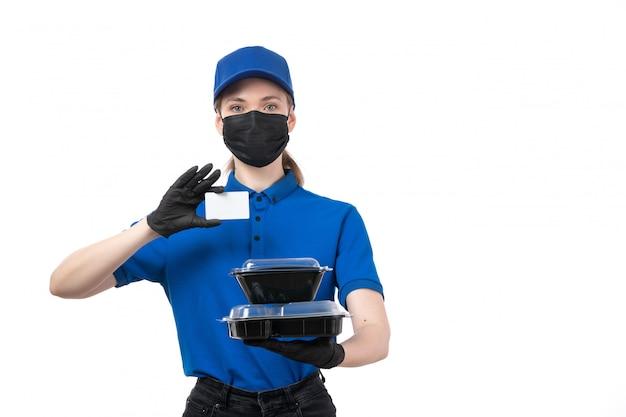 Молодая женщина-курьер в синей униформе, черные перчатки и черная маска, держащая миски для доставки еды и белую карточку, вид спереди