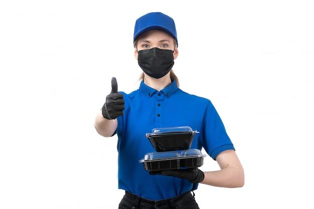 Молодая женщина-курьер в синей униформе, черные перчатки и черная маска, держащая миски для доставки еды, вид спереди