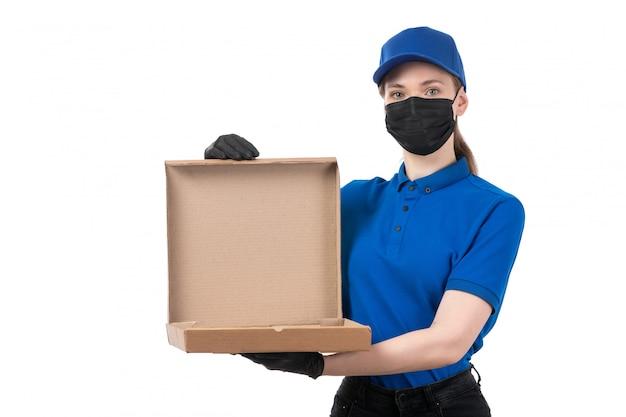 Молодая женщина-курьер в синей форме, черных перчатках и черной маске, держащая пакет для доставки еды, вид спереди