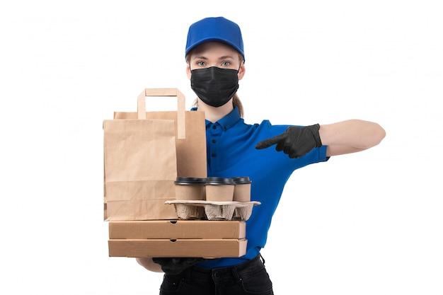 青い制服の黒い手袋とフードデリバリーパッケージを保持している黒いマスクの正面の若い女性の宅配便