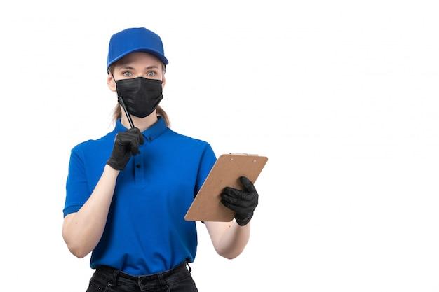 Вид спереди молодая женщина-курьер в синей форме, черные перчатки и черная маска, держащая блокнот