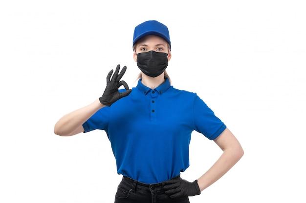 Вид спереди молодая женщина-курьер в синей форме, черные перчатки и черная маска позирует
