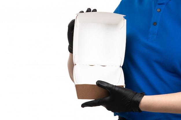 Молодая женщина-курьер в синей форме, черной маске и перчатках, держащая пустой пакет для доставки еды, вид спереди