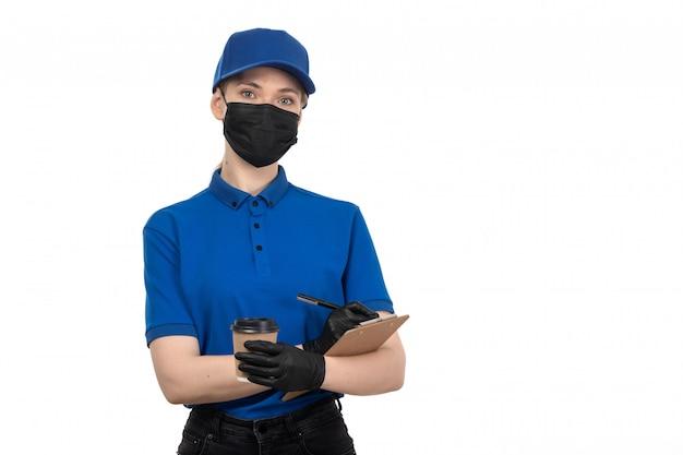Молодая женщина-курьер в синей униформе, черной маске и перчатках, держащая чашку кофе и блокнот, вид спереди