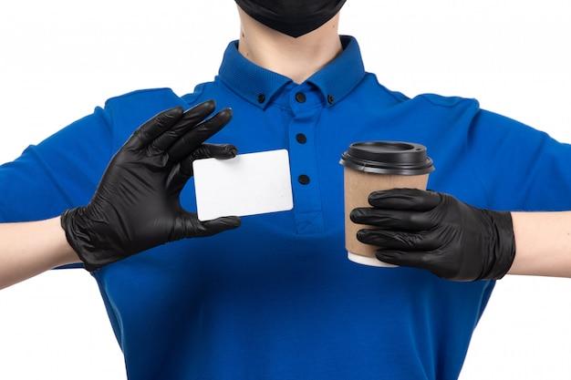Молодая женщина-курьер в синей форме, черной маске и перчатках, держащая чашку кофе и белую карточку, вид спереди