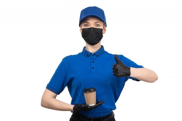 Молодая женщина-курьер в синей униформе, черной маске и перчатках, держащая чашку кофе, вид спереди